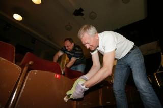 Ředitel divize BT Uwe Tilzen a generální ředitel Eduard Palíšek hrají tzv. žvejkačkovanou – odškrabávají zaschlé žvýkačky ze sedadel brněnského divadla Barka.