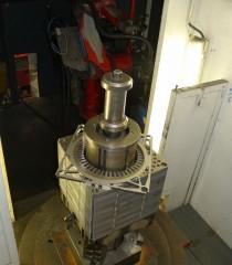Deska stolu svařovacího automatu, na níž jsou seskládány statorové plechy. V pozadí svařovací robot v klidové poloze.
